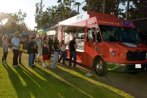 People enjoying meals from gourmet Food Trucks